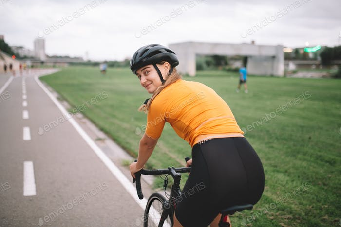 professional cyclist athlete on road bike look at camera and smiles. healthy female doing sport