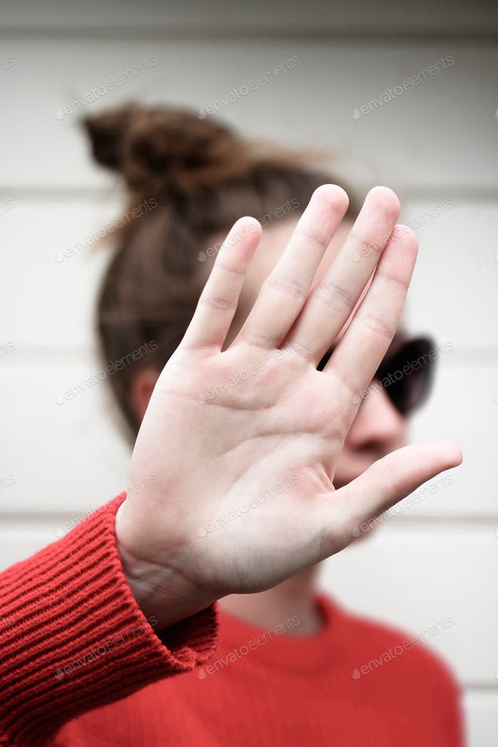 Girl holding her hand over her face. Hand gestures meaning no pictures filming, respecting privacy.