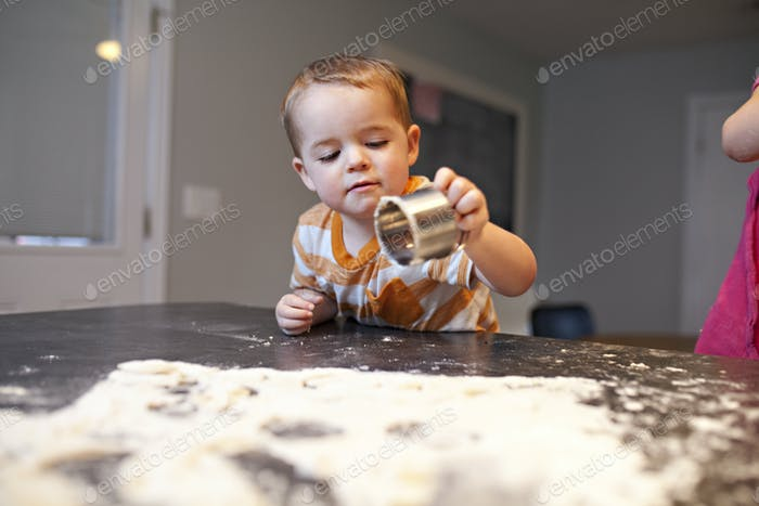 toddler boy cutting out cookies while making cookies