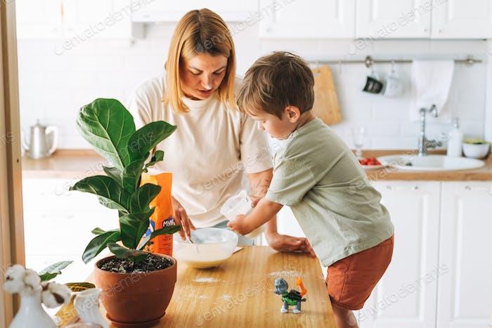 La joven y su hijo se divierten mientras cocinan con harina en la mesa en la cocina