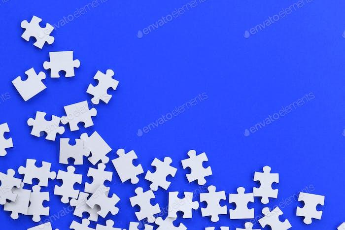 Puzzle blanco piezas dispersas sobre fondo azul cobalto, espacio de copia, superposición de texto