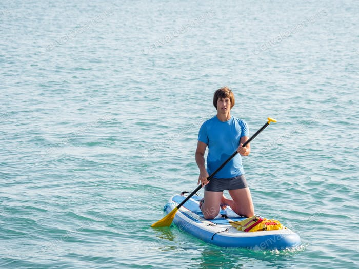 Paddle boarder. Sportsman paddling on knees on paddle board. SUP surfing. Active lifestyle.