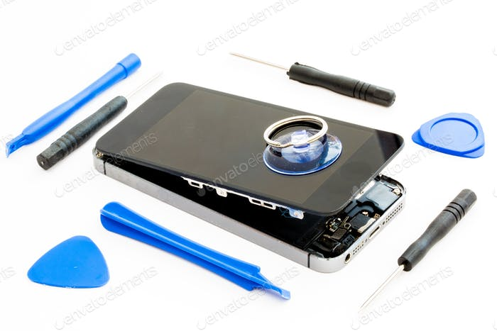 A damaged mobile or cell phone with all the tools needed to repair it