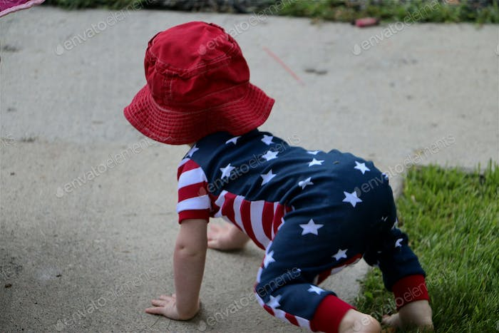 Image of baby in a patriotic romper crawling outside on Independence Day