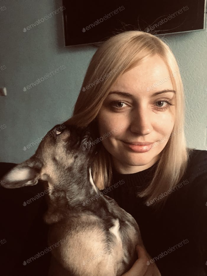 Pretty young woman with French bulldog puppy in the room. Lifestyle portrait