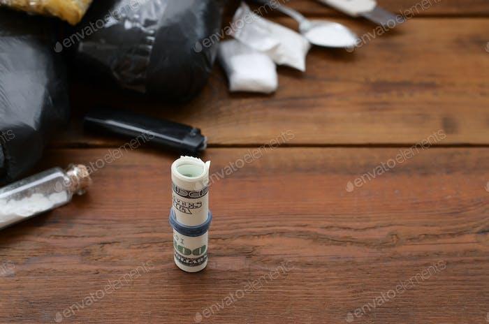 Roll of hundred dollar bills on background of narcotic drug dealer stuff