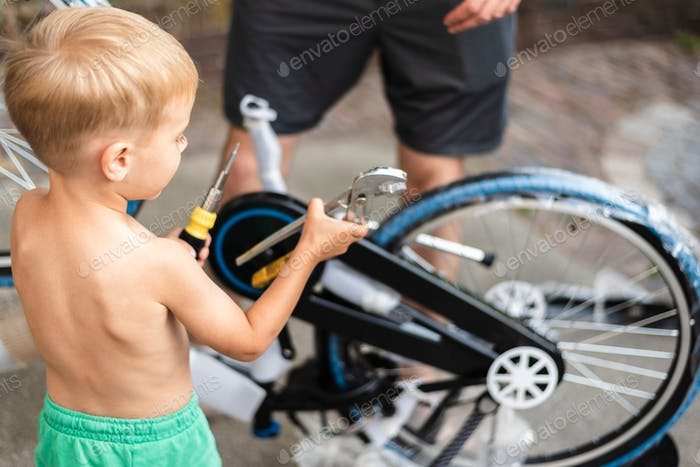 Little boy helps his dad to assemble new bicycle.