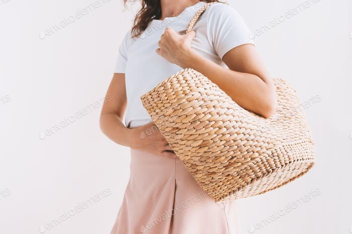 Fashionable stylish young woman in white t-shirt, pink pastel skirt holding straw rattan bag. Woman'