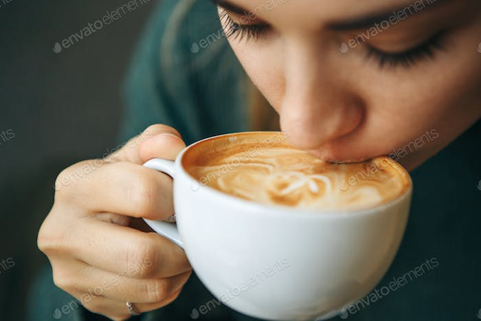 Close up portrait of a girl drinking cappuccino