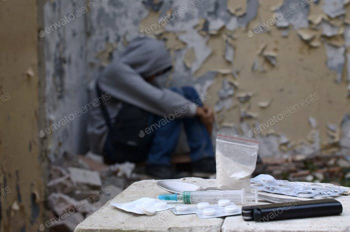 Young man in despair suffers from narcotic effects next to packs of heroin and many drug tablets