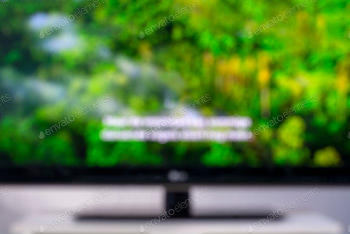 Blurred image of a television screen with a nature documentary and subtitles.
