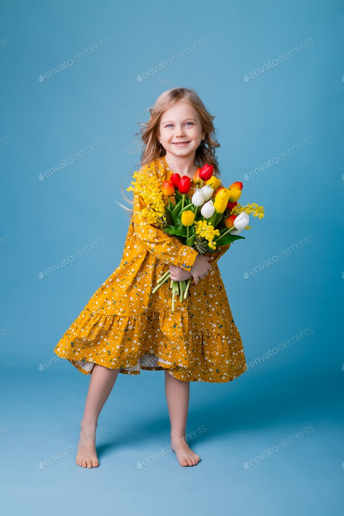 little blonde girl holds tulips in her hands. photo studio, blue background, text space