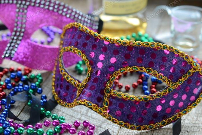 Mardi Gras mask and beads next to liquor bottle and shot glasses - Celebrating Fat Tuesday