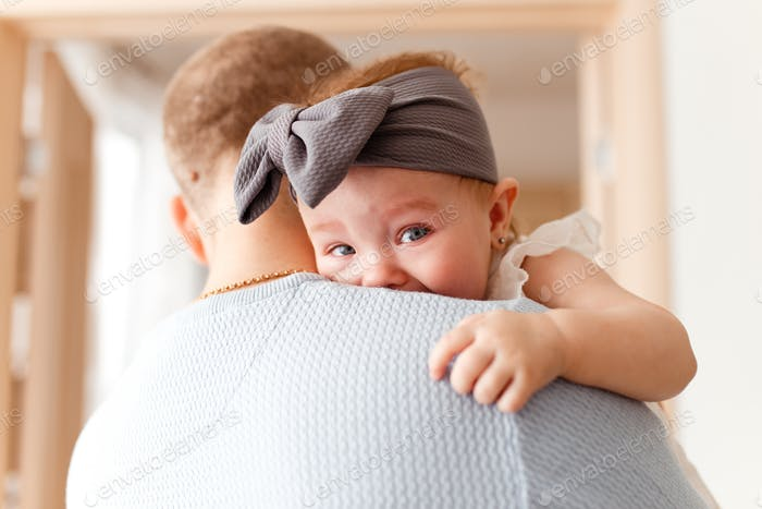 Dad and little daughter, Dad hugs and soothes his sad and bawled baby daughter with a bow on her hea