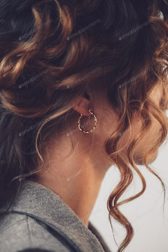 a woman with curly hair poses with jewelry. The concept of advertising jewelry. Minimalist lifestyle