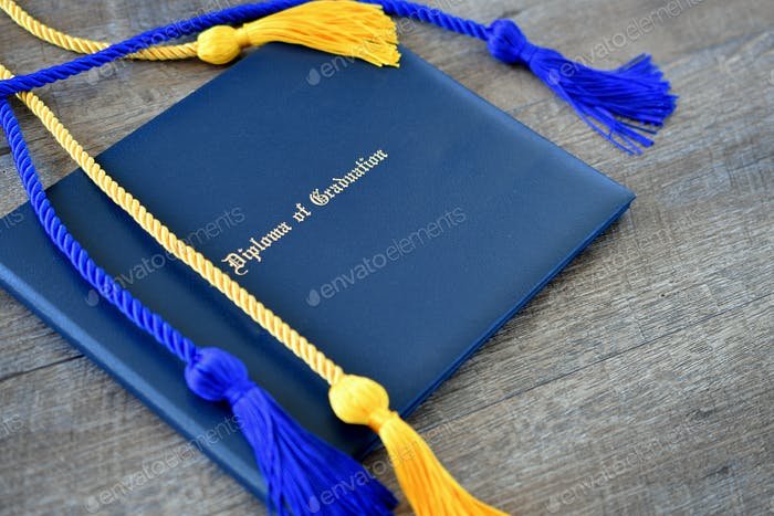 Flat lay of a Diploma of Graduation with honor cords on a simple wooden background.