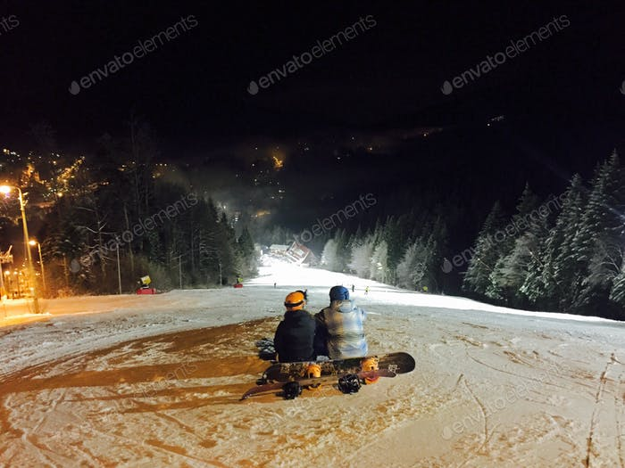 Couple of snowboarders resting on the ski slope at night