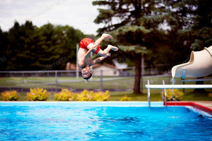 Boy doing a flip off of a diving board into a pool