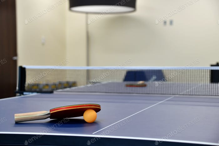 Ping pong paddle and ball on a ping pong table. Clean, modern game room, break room, recreation area