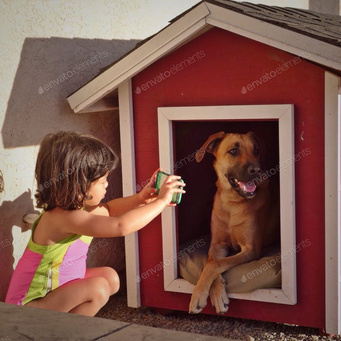 Little girl takes a picture of her dog.