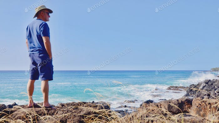 Senior spending time on a rocky shoreline contemplating retirement and life.