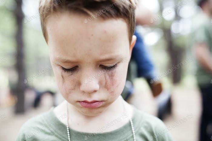 Junge weint mit Tränenstreifen ins Gesicht