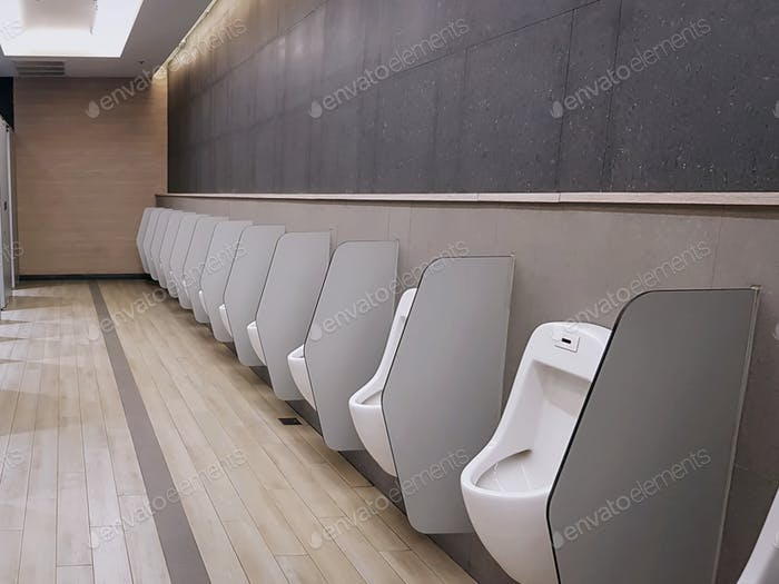Row of Urinals with Partitions inside Men's Toilet