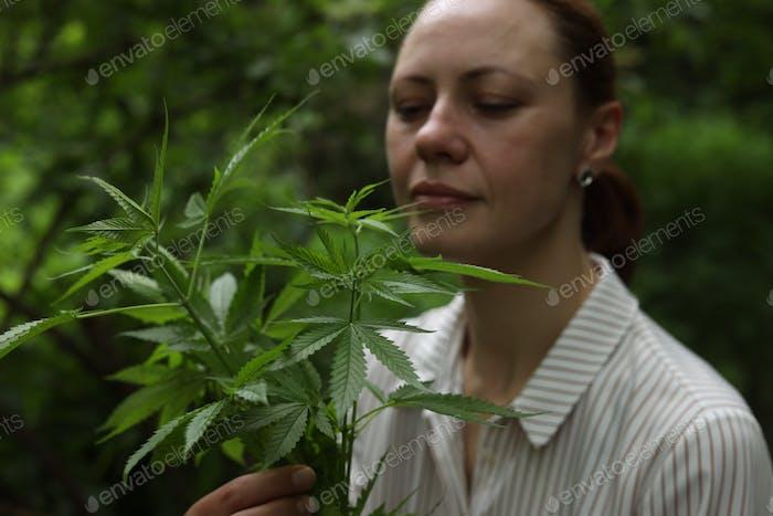 A girl sniffs marijuana. hemp. Legalization of marijuana, use for medical purposes.