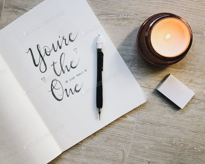 Calligraphy and scripted writing in a notebook with a mechanical pencil and candle with matches.