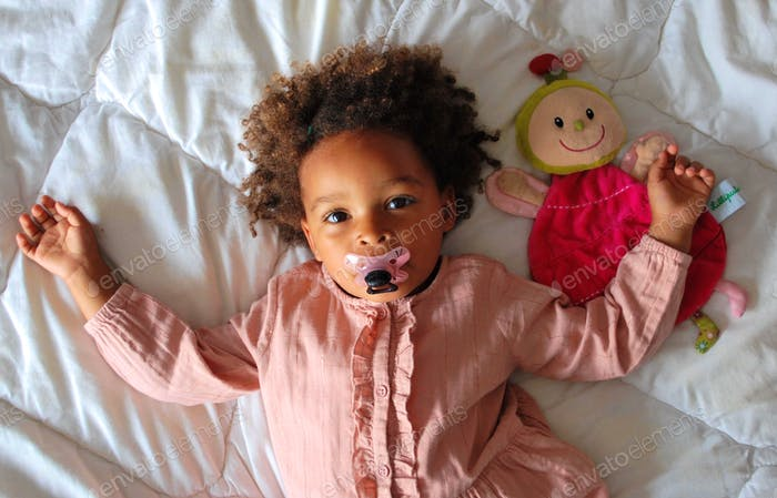 Cute little girl of mixed origin lying on a bed with her cuddly toy