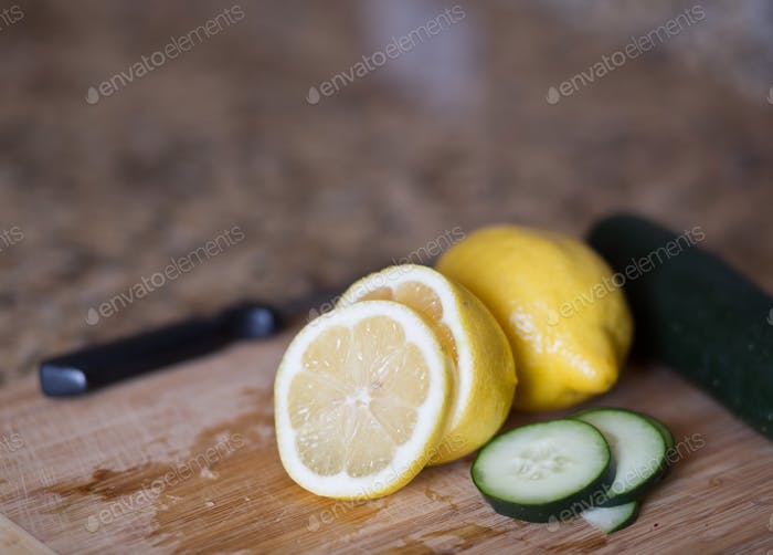 Sliced cucumbers and lemons on a cutting board.
