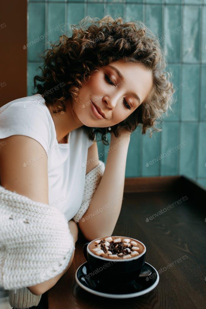 schöne glücklich lockig gebräunt junge Mädchen Student Influencer in einem weißen T-Shirt und Pullover sitzen