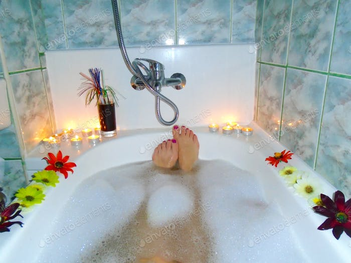 Woman's feet with red nail polish in bubble bath with candles and flowers