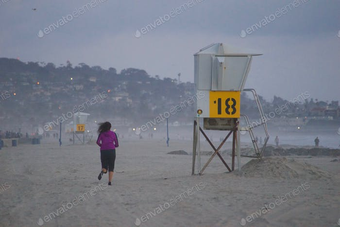 A woman in purple is jogging in the early morning hours on Mission Beach, San Diego California