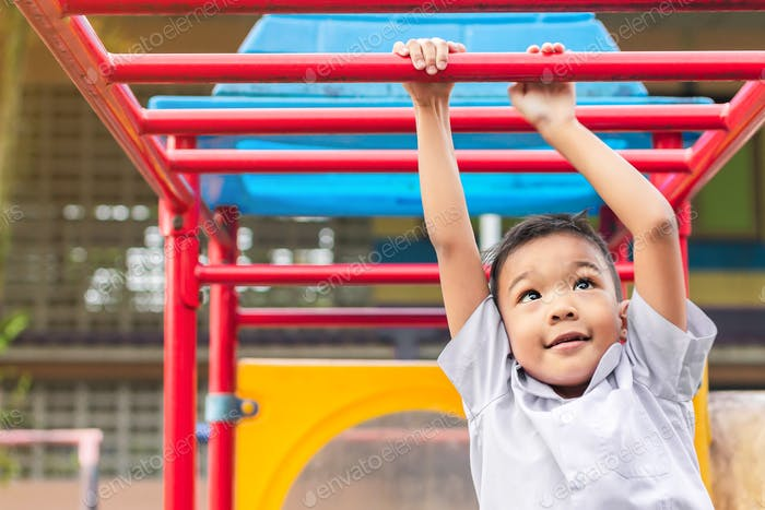 Happy Asian child boy playing and hanging from steel bar toy at the playground.