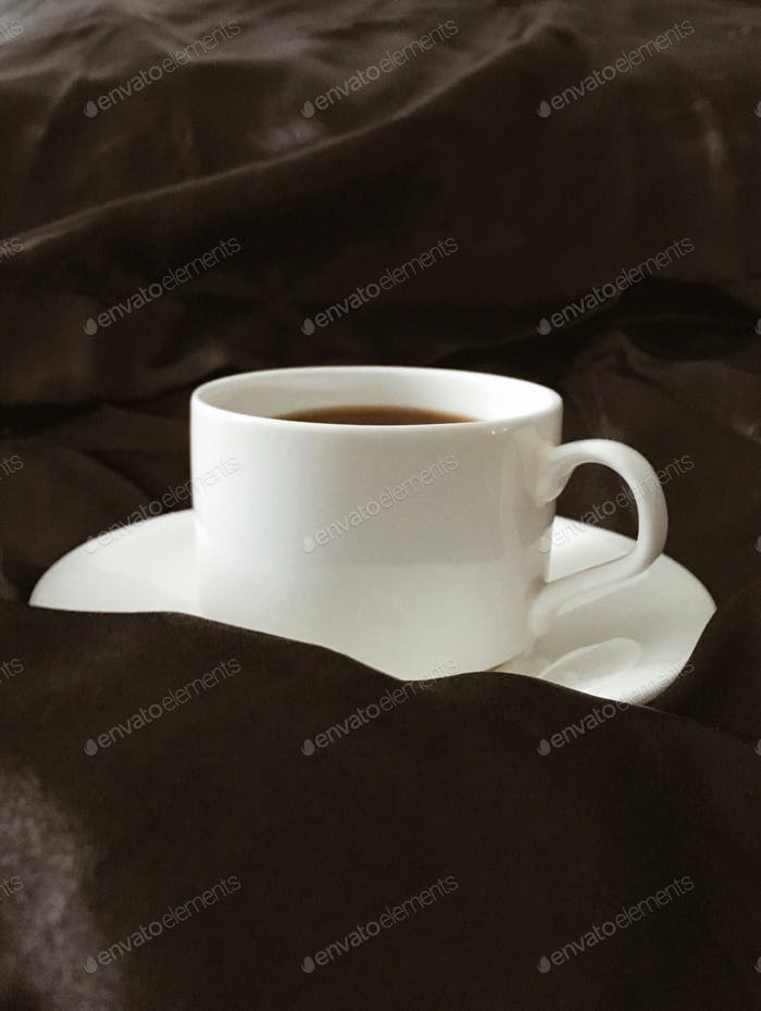 White porcelain cup on the black satin sheets. Morning coffee
