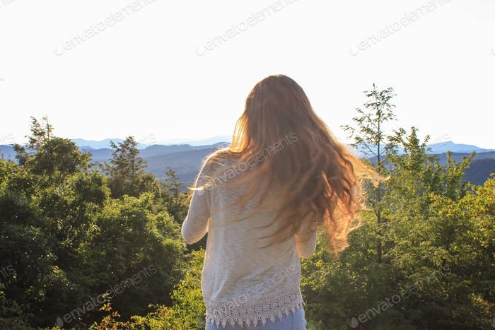 Young woman hiking atop a mountain at golden hour with sun highlighting her hair blowing in the wind