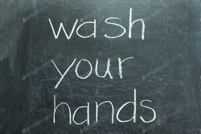 Wash your hands written on chalkboard