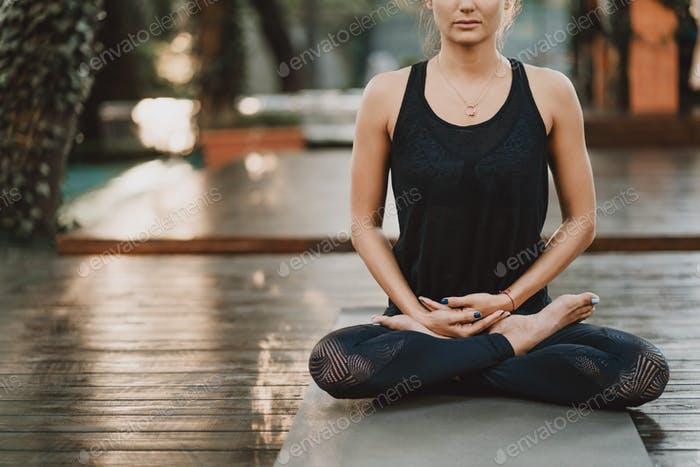 Concentrated girl sitting in lotus pose and meditating or praying. Young woman practicing yoga alone