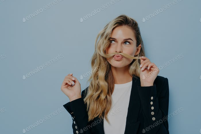 Funny joyful blonde woman having fun while posing against blue studio wall, playing with strand of h