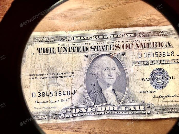 Blick auf eine Ein-Dollar-Schein durch eine Lupe 🔎 💵 💴 💰