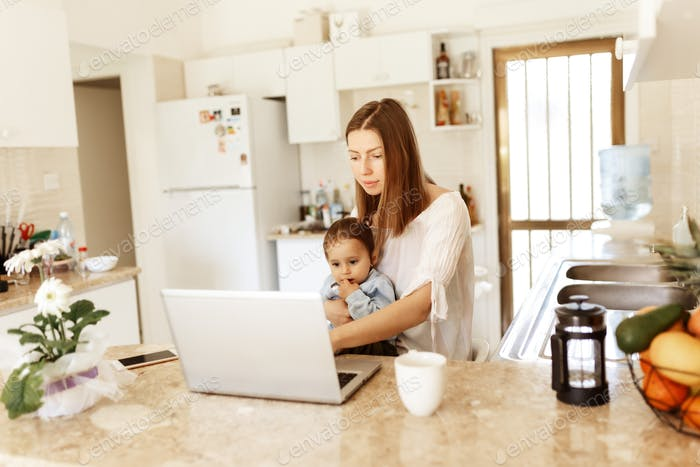 young woman with baby using laptop . Blogger, writer, journalist, student girl working on computer a