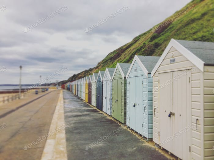 Pastel colourful sheds on seaside front fading into diminishing perspective.