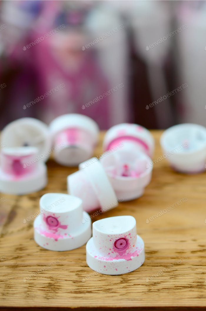 The soiled pink nozzles from the paint sprayer lies on a wooden plank on a background of a many