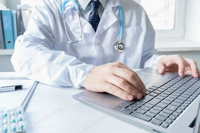 Doctor types, speaks, talks to patient by laptop. Telehealth,telemedicine,online consultation,video