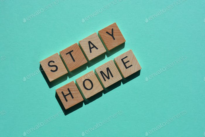 Stay Home, in 3D wood alphabet letters on a green background