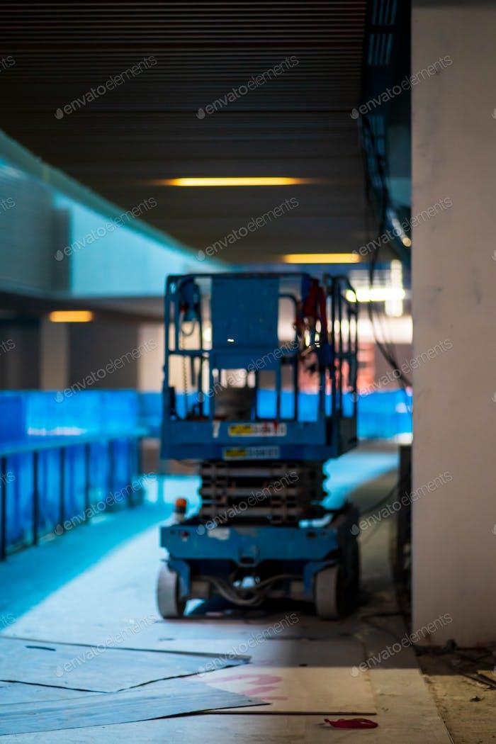 Foto borrosa del elevador de tijera en una obra de construcción.