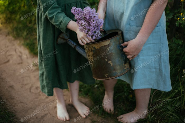 Bare feet of two girls on a village road with a watering can from which a bouquet of lilacs sticks o