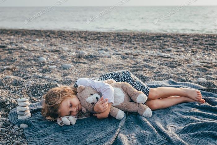The todler girl fell asleep on the beach