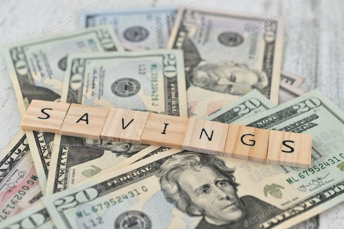 Savings, save money letter tiles on money - currency cash, prosperity, assets, business, retirement
